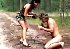 Shoes slave cleans mistress shoes of mud outdoors