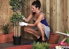 Brunette hot lady takes care of plants and flashes her booty upskirt