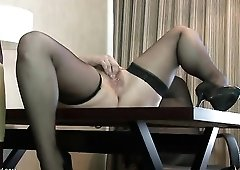 Stockings babe on a hotel desk masturbates her cunt